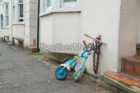 zwei kinderroller in einer strasse angekettet