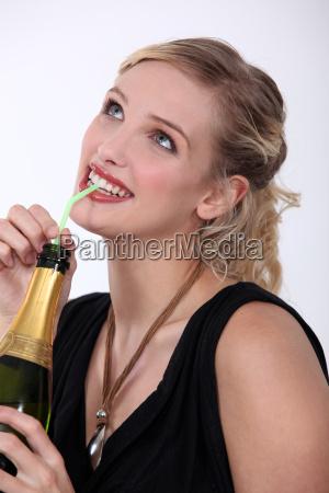 frau trinkt champagner mit strohhalm