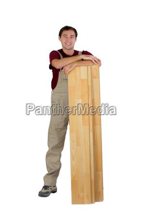 worker with wooden floorboards