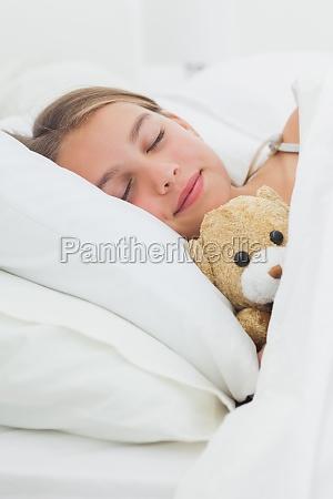 nettes maedchen schlaeft mit ihrem teddybaeren