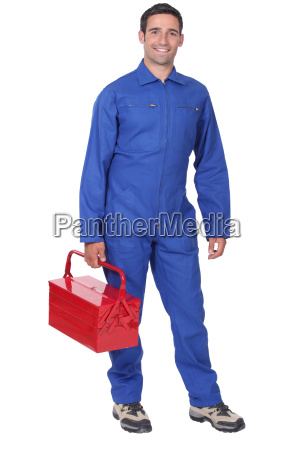 man wearing blue overalls holding tool