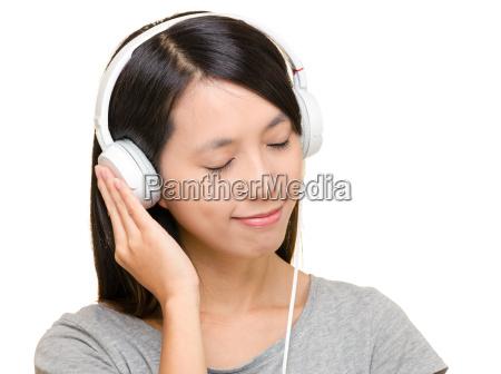 asiatische frau die musik hoeren