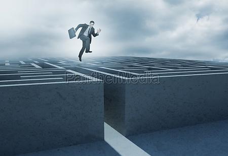 geschaeftsmann springt ueber ein labyrinth