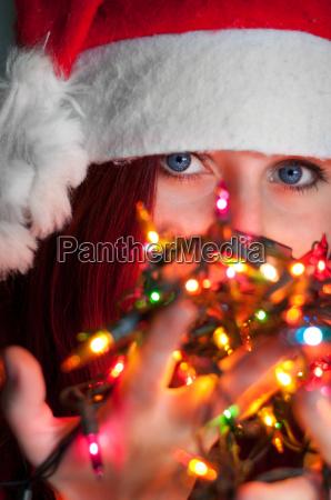 frau mit weihnachtslichterkette leuchtet