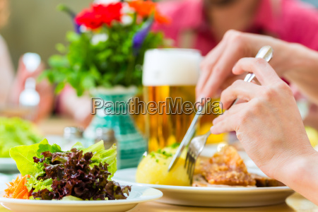 people in bavarian tracht eating in