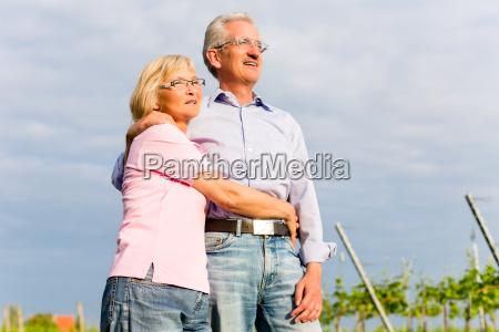 happy seniors are sitting in vineyard