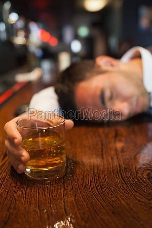betrunkener geschaeftsmann haelt whisky auf einen