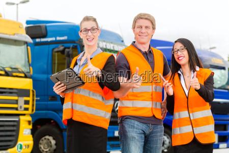 spediteure vor lastwagen und lkw auf