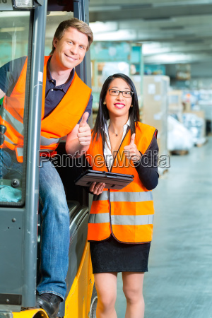 staplerfahrer und kollegin in lager von