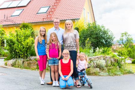 glueckliche familie vor einfamilienhaus