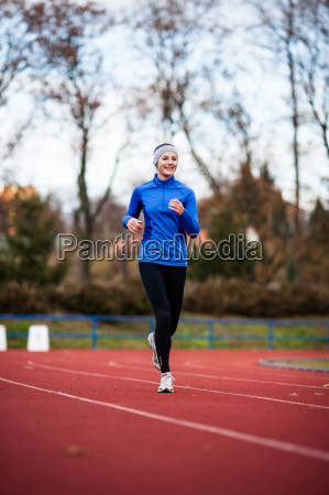 young woman running at a track