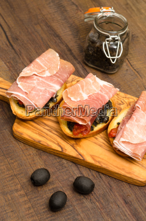snack with raw ham and olive