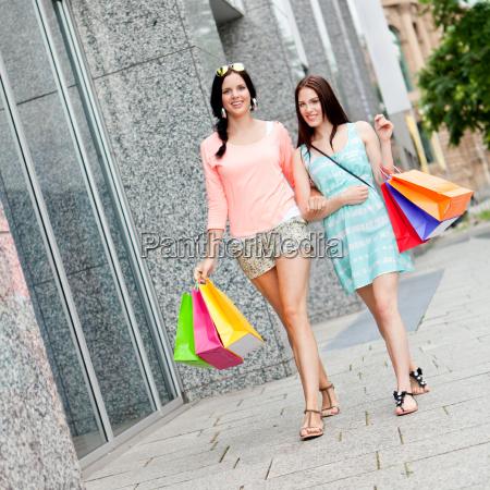 junge lachende frauen beim shopping im