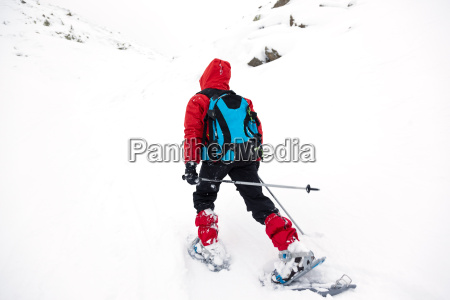 boy hikes in mountain with snowshoe