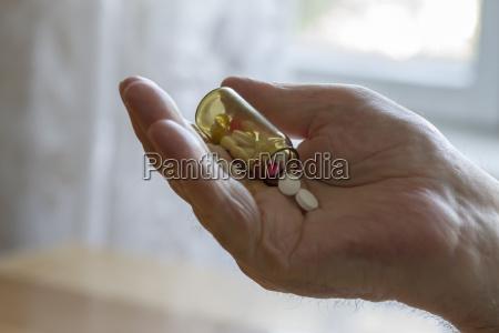 old man holding pills
