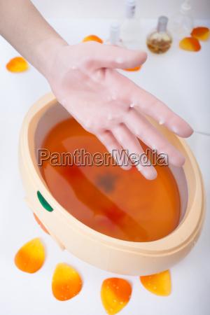 weibliche hand orange paraffin wachs in