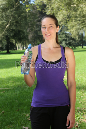 young woman with bottle in sports
