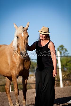 junge weibliche reiterin trainiert ihr pferd