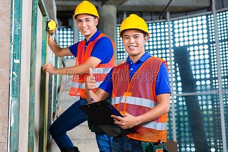 asiatische arbeiter auf der baustelle zu