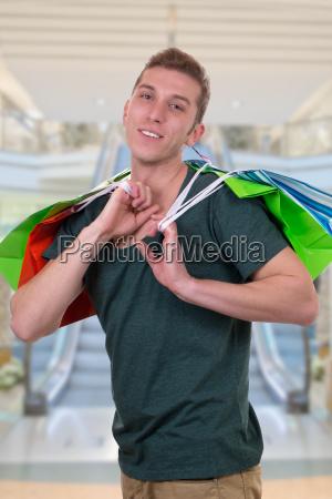 junger mann mit einkaufstaschen in shopping