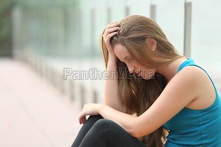 teenager maedchen sitzen im freien deprimiert