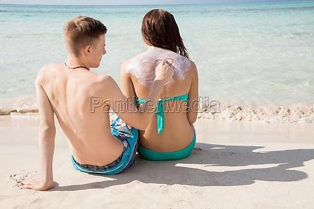 junges verliebtes paar am strand sonnenschutz