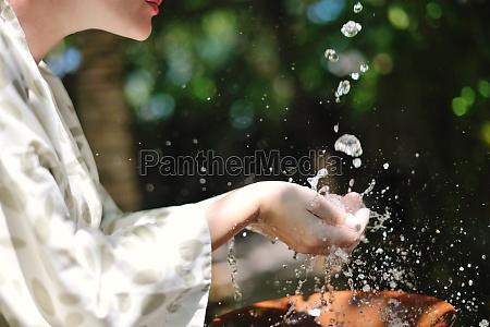 spritzwasser frischem wasser auf frauenhaenden