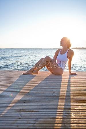attraktive frau sitzen auf pier