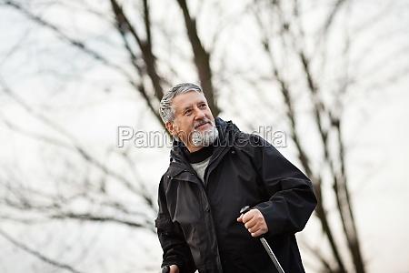 aelterer mann nordic walking im freien