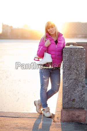 blond woman standing with ice skates