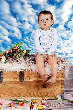 kind auf truhe vor blauen himmel
