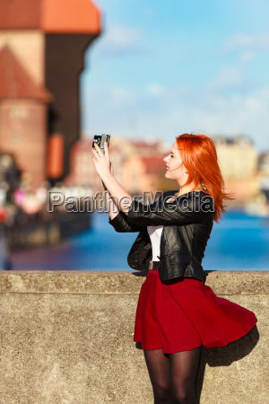 fashionable tourist girl taking picture with