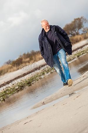 lachender gluecklicher aktiver rentner senior aelterer