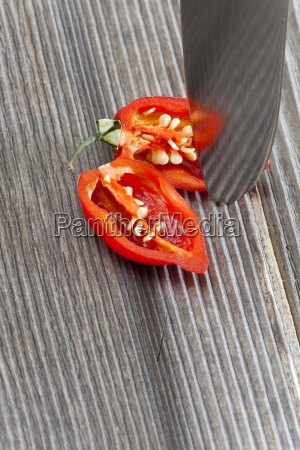 halved habanero chili pepper on wooden