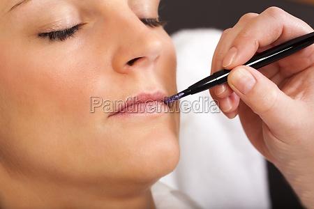 farbe wird mit pinsel auf lippen