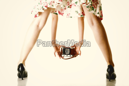 womans legs and vintage camera