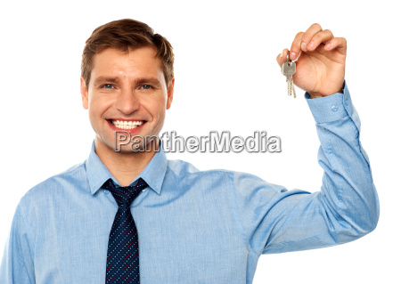 portrait of smiling businessman holding keys