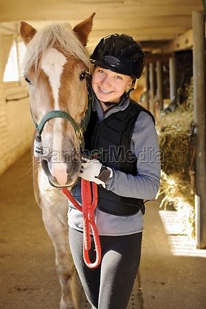 reiter mit pferd im stall