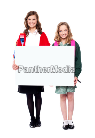 schoolgirls holding big blank banner ad