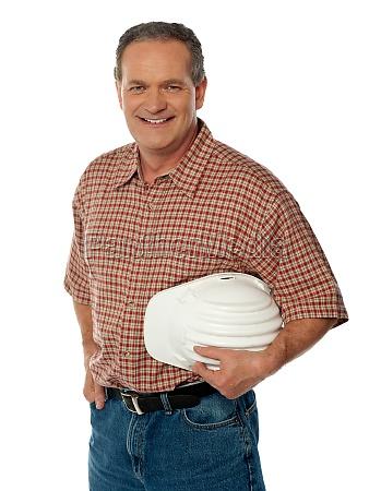 smiling senior architect holding white safety