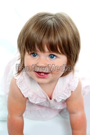 baby girl with milk teeth crawling