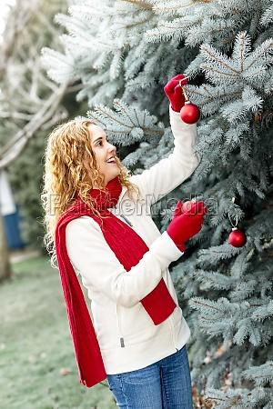 frau schmuecken weihnachtsbaum ausserhalb