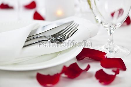 romantische abendesseneinstellung mit den rosafarbenen blumenblaettern