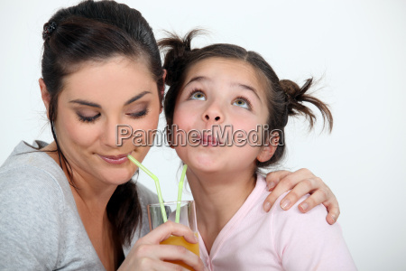 mother and daughter sharing a drink