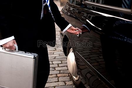 man opening door of taxi cab