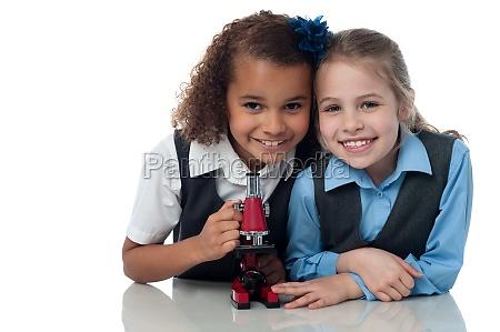 junge kleine schulmaedchen mit mikroskop
