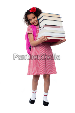 cute little schoolgirl carrying stack of