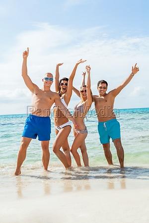 gruppe lachender junger leute am strand