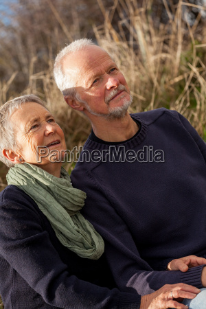 happy relaxed elderly couple outdoors in