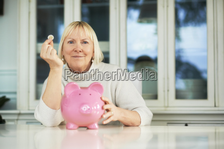 old woman showing piggybank and euro